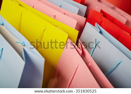 Colourful paper shopping bags isolated on red - stock photo