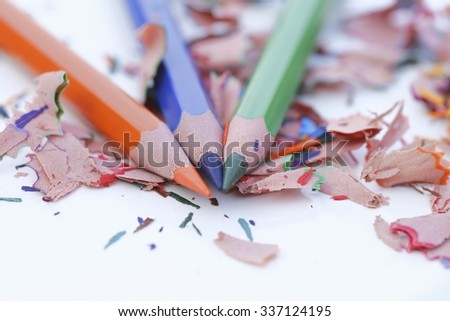 Colourful pencils and colourful wood shavings on white background  - stock photo