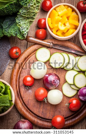 Colourful peppers, zucchini and onions on a chopping board. - stock photo