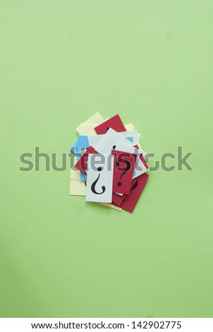 colourful question marks on green paper  - stock photo