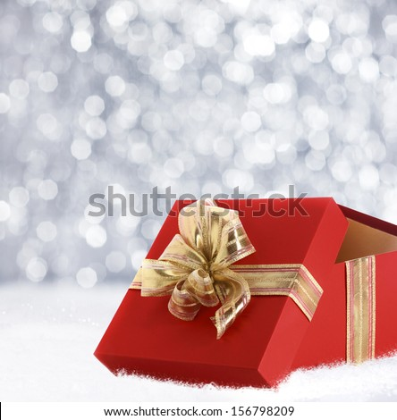Colourful red Christmas gift decorated with a gold ribbon and bow in winter snow with a bokeh of falling snowflakes and copyspace for your seasonal greeting - stock photo