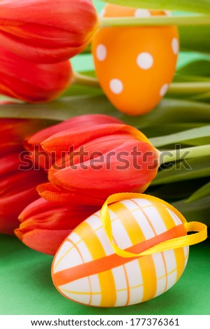 Colourful red Easter still life with delicate fresh spring tulips and handpainted traditional Easter Eggs arranged on a white background with copyspace for your seasonal wishes - stock photo