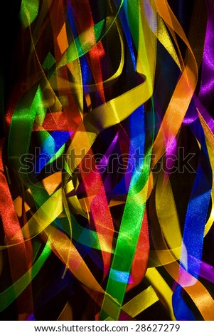 colourful ribbons lit against a dark background - stock photo