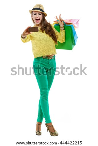 Colourful shopping vibes. Excited brunette woman in hat and bright clothes with colorful shopping bags showing victory gesture and taking selfie with smartphone against white background
