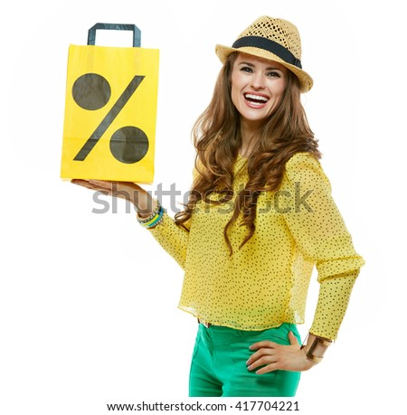 Colourful shopping vibes. Portraits of smiling brunette woman in hat and bright clothes showing shopping bag symbolising beginning of the sales - stock photo
