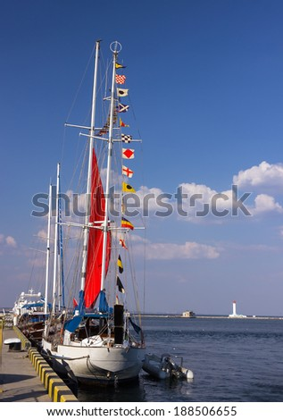 Colourful signal flags on a sailing boat and lighthouse - stock photo
