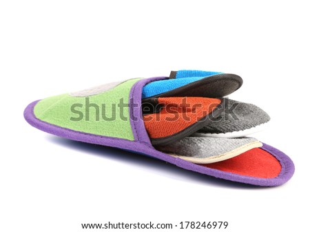 Colourful slippers into big slipper. Isolated on a white background. - stock photo