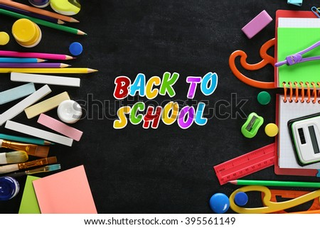 Colourful stationery on blackboard background