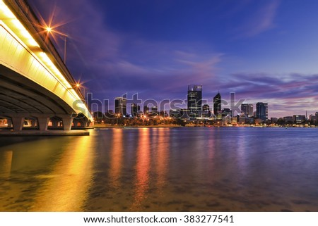 colourful sunrise over Perth city CBD with connecting bridge across Swan river. Bright lights reflecting in still clean water showing shallow riverbed