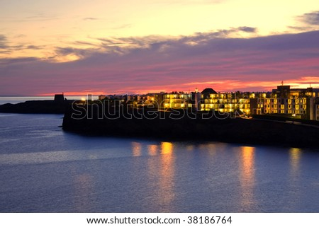 Colourful sunset view of a beach with reflexes in the sea of Lanzarote island - stock photo