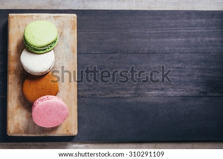 Colourful tasty macaroons on a wooden table. Top view - stock photo