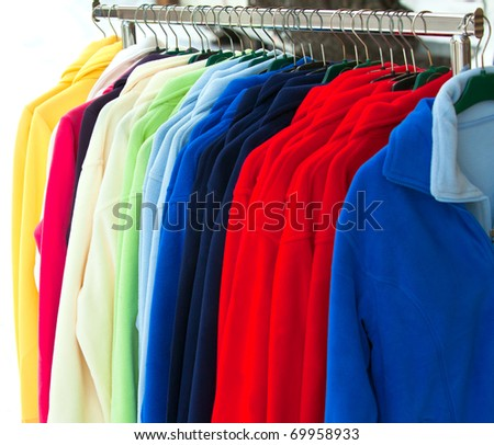 Colourful Textile sport shirts hanging in row at store - stock photo