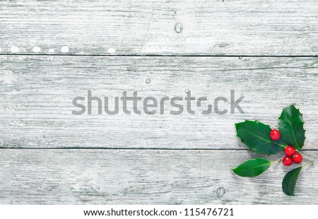 Colourful traditional Christmas holly with with red berries on grunge wood texture of old weathered boards with copyspace - stock photo