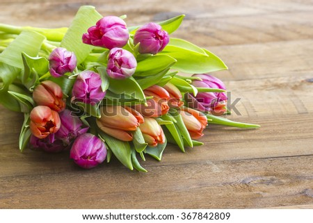 colourful tulips on wooden background - stock photo