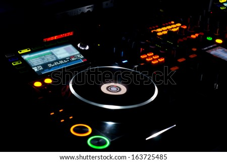 Colourful turntable and LP vinyl record on a DJ music deck at a disco, concert or party for mixing music and recorded soundtracks - stock photo