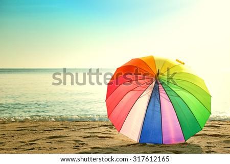 Colourful umbrella on the beach retro style - stock photo