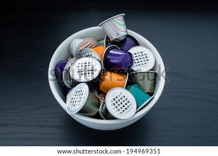 Colourful used gourmet coffe capsules in a bowl on dark wooden table - stock photo