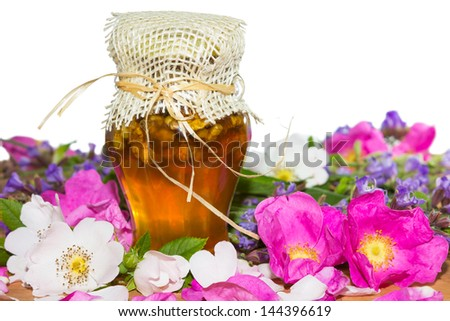 Colourfull image of a Honey jar with blossoms of rosa canina and herbs, on white backgrond. - stock photo
