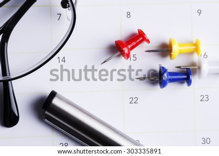 Colourfull push pin with red push pin pointed to 14th day of the month with a pen and spectacles, valentine's day and anniversary concept
