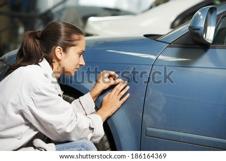 colourist woman matching paint of car element at automobile repair and renew service station with color example cards - stock photo