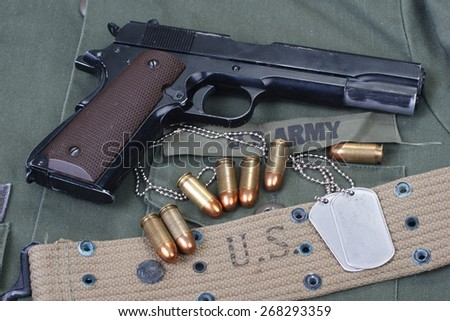 colt government M1911 with US ARMY uniform texture background - stock photo