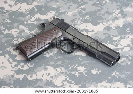 colt 1911 handgun on camouflage uniform - stock photo