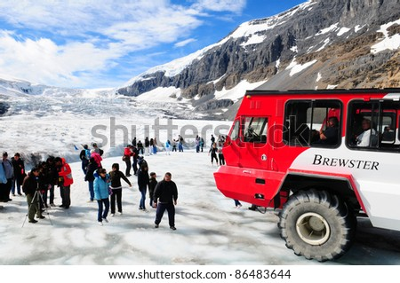 COLUMBIA ICEFIELDS, CANADA-AUGUST 21: Massive Ice Explorers, specially designed for glacial travel, take tourists onto the surface of the Athabasca Glacier (located int he Canadian Rockies) on August 21, 2011 in the Columbia Icefields, Canada. - stock photo
