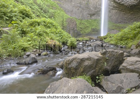 Columbia River Gorge waterfall rock and green plants. - stock photo