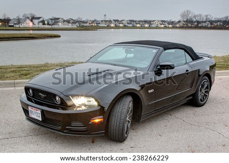 COLUMBUS, OHIO - CIRCA DECEMBER 14, 2014: A black 2014 Ford Mustang GT convertible idle on a road near lake at sunrise.  - stock photo