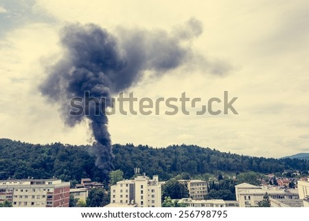 Column of black smoke rising above a forest nearresidential area. - stock photo