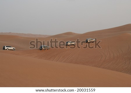 Column of jeeps travelling in sand dunes - stock photo