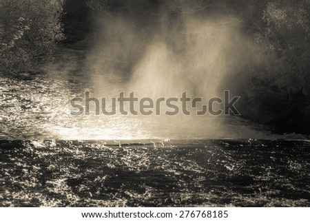 Column of mist generated by a waterfall in Monfero (Spain), strongly illuminated by evening light. The scene intentionally has an antique look to remember the pictures of the early explorers.