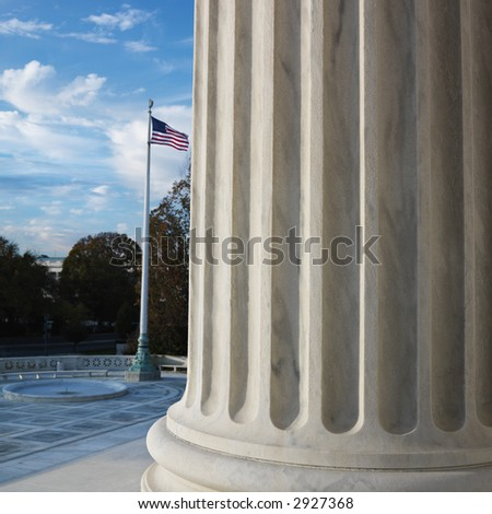 Column of Supreme Court building with American flag in Washington D.C. - stock photo