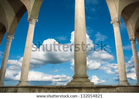 columns and arches of ancient roman building on blue sky