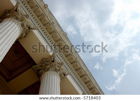 Columns and detail of a historical building, with cloudy blue sky