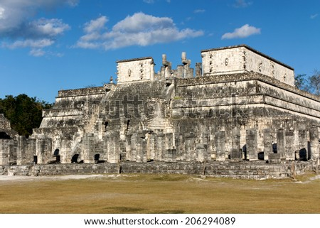 Columns in the foreground before the Temple of the Warriors at the Mayan site of Chichen Itza, Yucatan, Mexico. - stock photo