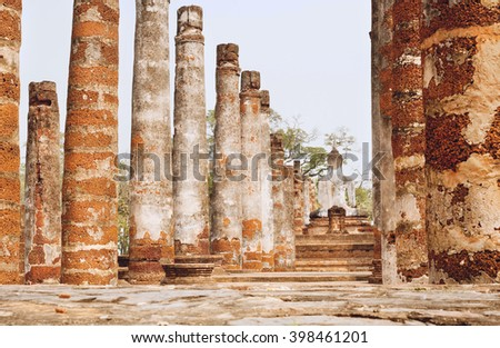 Columns of ancient ruined temple Wat Maha That with back of stone Buddha statues at Sukhothai historical park. UNESCO World Heritage Site.  - stock photo