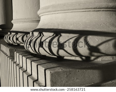 Columns of St. Louis Cathedral in New Orleans with shadow cast by wrought iron fence. - stock photo