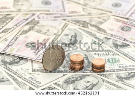Columns of the cents coins and one silver collection dollar on the hundreds and fifty dollars banknotes - stock photo