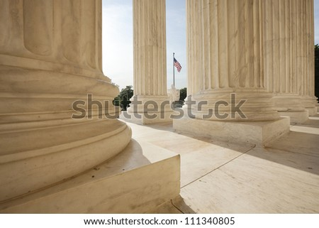 Columns of the Supreme Court building in Washington DC frame an American flag - stock photo