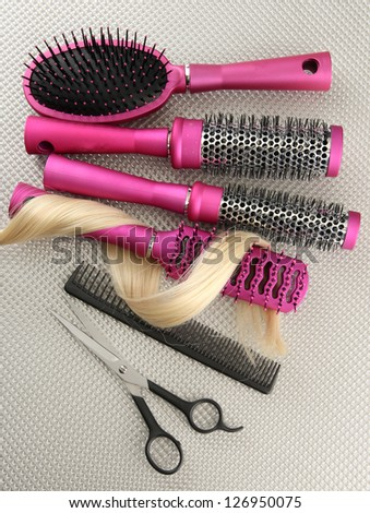 Comb brushes, hair and cutting shears, on grey background - stock photo