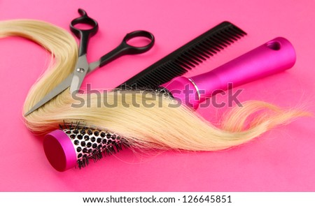Comb brushes, hair and cutting shears, on pink background - stock photo