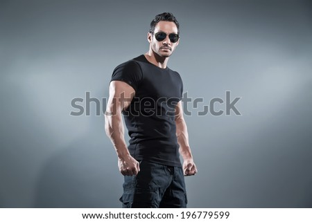 Combat muscled action hero man wearing black t-shirt with pants and sunglasses. Studio shot against grey. - stock photo