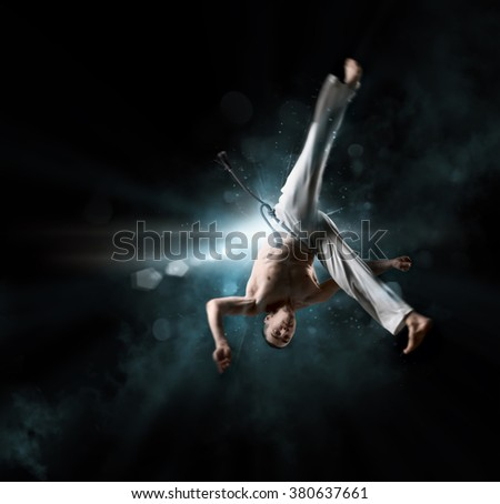combative sport: male fighter trains capoeira on a black background - stock photo