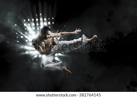 combative sport: male fighter trains capoeira on a black background in the light - stock photo
