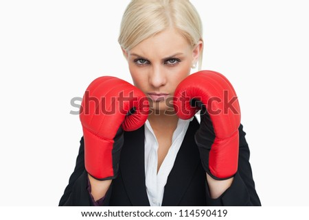 Combative woman with red gloves fighting against white background - stock photo