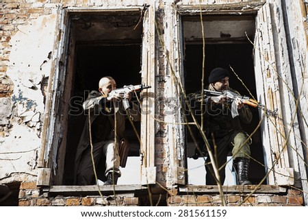 Combats shooting out of the ruined windows - stock photo