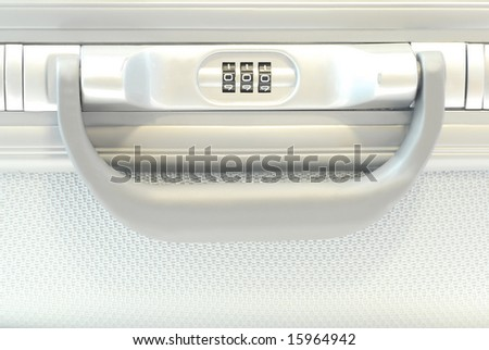 Combination lock and handle of a silver colored suitcase - stock photo