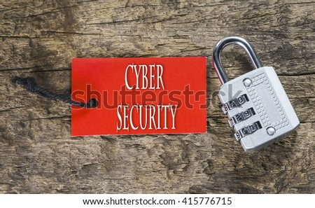 Combination number padlock on wood background with Cyber Security written on label tag - stock photo