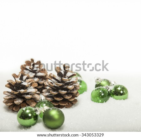 combination of pine cones and green christmas balls in snow - stock photo